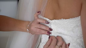 Mother buttoning the bride`s wedding dress stock video footage