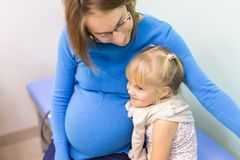 Mother calming daughter before vaccination. At hospital Royalty Free Stock Photography