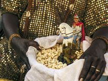 Candomble. Mother of Candomble saint holds a basket with popcorn and the image of Saint George (Ogum) in front of the Church Stock Photography