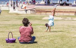 Mother Captures Daughter. Performing a cart wheel At Montgomery, Alabama River Walk park during pre-Easter festival Stock Photo