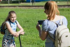Mother captures film with daughter on mobilephone for sending to father. Summer park Royalty Free Stock Photos