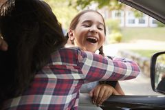 Mother In Car Collecting Daughter In Front Of School Gates royalty free stock photography