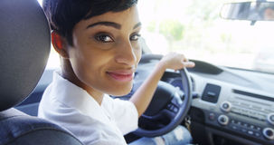Mother in car looking over shoulder smiling Royalty Free Stock Images
