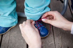 Mother care - tying a shoe Stock Photography