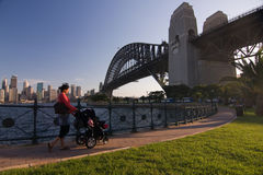 Mother care - Walking with the pram. Young mother is walking with the pram under the Famous Sydney Harbour Bridge. City skyline at the distance stock photos
