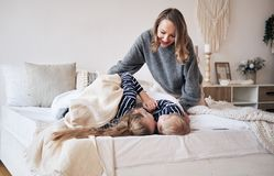 Free Mother Care. Young Mother Covering Children With A Blanket In Bedroom. Brother And Sister Embracing And Sleeping On The Bed. Stock Photography - 132535272