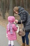 Mother cares for her daughter in the open air Stock Photo