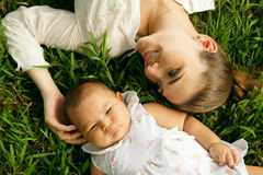 Mother With Caressing Baby Daughter Laying On Grass Stock Photography