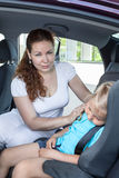 Mother caressing her daughter sleeping in the car seat safety Stock Images