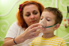 Mother caring kid with aerosols inhalation Royalty Free Stock Photo