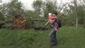 A mother carries a child near the wind toppled trees stock video
