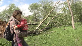 A mother carries a child near the wind toppled trees stock video footage