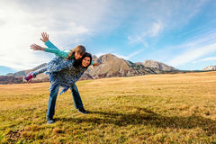 Mother carries daughter on her back  in Durmitor, Montenegro Royalty Free Stock Photos