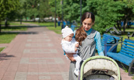 Mother carries her daughter and stroller wheels Royalty Free Stock Photos