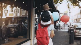 Mother carries son on shoulders along the street. Girl walks with a little happy kid in hat and two air balloons. 4K. Mother carries son on shoulders along the stock footage