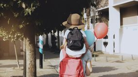 Mother carries son on shoulders among houses. Woman walking with a kid in hat and two air balloons. Lifestyle 4K. Mother carries son on shoulders among houses stock video footage