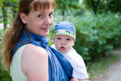 Mother carry baby in sling. (strap of cloth used to carry baby under 2 years Royalty Free Stock Photo