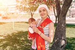 Mother carry a infant baby in wrap sling in park. Springtime. Concept of natural parenting. Happy family spring concept Stock Photos