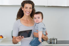 Mother carrying baby boy while holding digital tablet Stock Photo