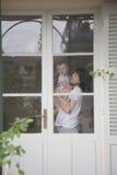 Mother Carrying Baby In Front Of Door Stock Photo