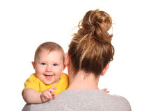 Mother carrying baby girl looking over shoulder. Cutout Royalty Free Stock Images