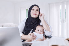 Mother Carrying Baby while Working Royalty Free Stock Photo