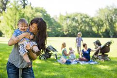 Mother Carrying Cheerful Baby Boy At Park. Mother carrying cheerful baby boy with friends and children in background at park Stock Image