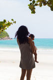 Mother carrying a child to sea Royalty Free Stock Images