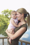 Mother Carrying Daughter Against Lake Royalty Free Stock Image