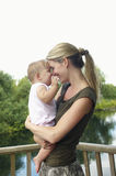 Mother Carrying Daughter On Balcony Against Lake Royalty Free Stock Photo