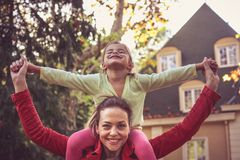Mother carrying daughter on piggyback. Stock Photo