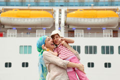 Mother carrying daughter, ship on background Stock Photo