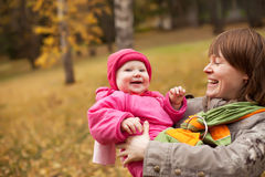 Mother carrying daughter in sling Stock Image
