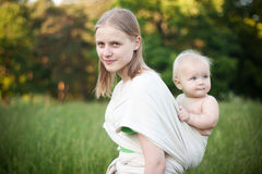 Mother carrying daughter in sling in field Royalty Free Stock Image