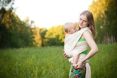 Mother carrying daughter in sling in field