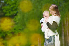 Mother carrying daughter in sling in park Stock Photography