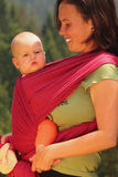 Mother carrying her baby in a sling Royalty Free Stock Images