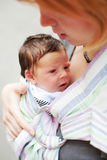 Mother carrying her baby in a sling. Young mother carrying her sweet baby in a sling Royalty Free Stock Photos