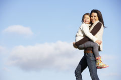 Mother Carrying Her Daughter Royalty Free Stock Photography