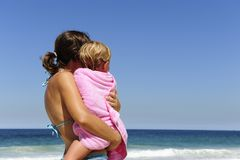 Mother carrying her daughter on the beach Stock Image
