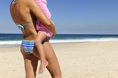 Mother carrying her daughter on the beach Stock Images