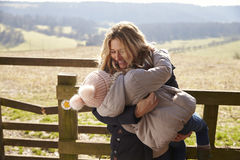 Mother carrying her daughter by a gate in the countryside Stock Images