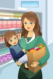 Mother carrying her daughter and grocery bags Stock Photo