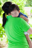 Mother carrying her daughter in home backyard Stock Photos