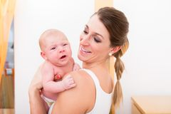 Mother carrying her newborn baby royalty free stock images