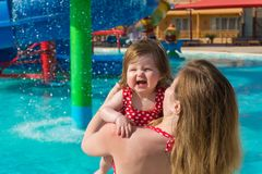 Laughting baby and mother in water park. Mother carrying laughting baby girl while standing in pool in water park on sunny day on resort stock image