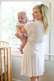 Mother carrying seven month old baby beside crib Royalty Free Stock Image