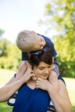 Mother Carrying Son On Shoulders In Park Stock Photography