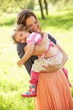 Mother Carrying Young Daughter Stock Photos