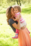 Mother Carrying Young Daughter In Field Stock Images
